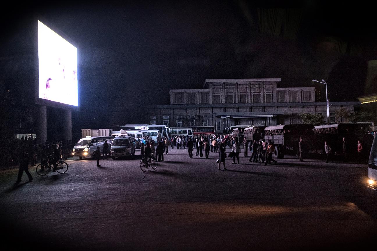 Militär und Zivilisten schauen sich eine Übertragung auf einem Bildschirm in der Nähe des Bahnhofs Pyöngyang an.